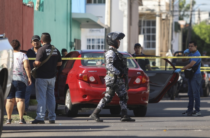 Police and forensic personnel work the crime scene where journalist Marcos Miranda was kidnapped, in Boca del Rio, Veracruz state, Mexico, Wednesday, June 12, 2019. Miranda was abducted this morning from his home by armed men, according to the Network of Veracruz Journalists. (AP Photo/Felix Marquez)