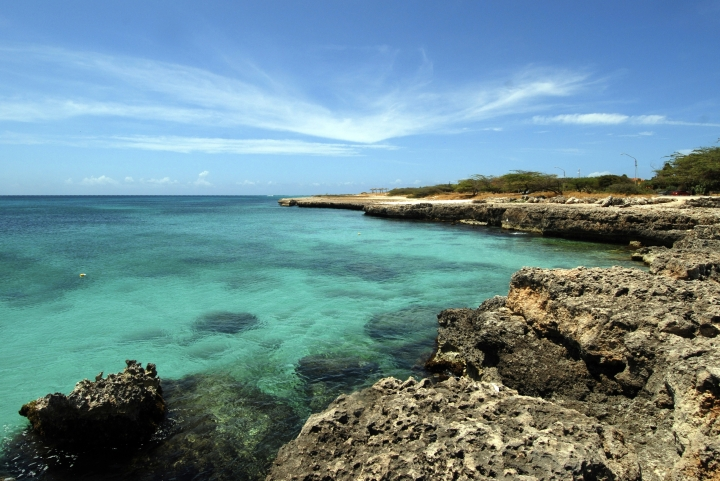 FILE - In this April 2008 file photo, crystal clear water meets the shore in Aruba. Aruba offers a sun-drenched Caribbean escape outside the hurricane belt, making this island retreat an irresistible option for late-summer travelers. (AP Photo/Shoun A. Hill, File)