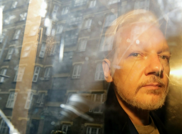 FILE - In this file photo dated Wednesday May 1, 2019, buildings are reflected in the window as WikiLeaks founder Julian Assange is taken from court, where he appeared on charges of jumping British bail seven years ago, in London. 47-year old Assange is expected to appear via a video link at court Friday June 14, 2019, as he continues his fight against extradition to the United States, where he faces prosecution under the Espionage Act. (AP Photo/Matt Dunham, FILE)