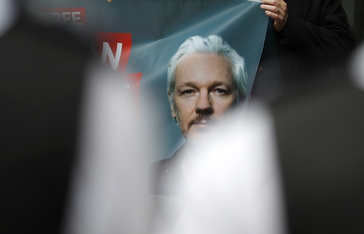 Police watch Assange supporters protesting outside Westminster Magistrates Court in London, Friday, June 14, 2019. WikiLeaks founder Julian Assange is expected to appear via a video link at court Friday, as he continues his fight against extradition to the United States, where he faces prosecution under the Espionage Act.(AP Photo/Frank Augstein)
