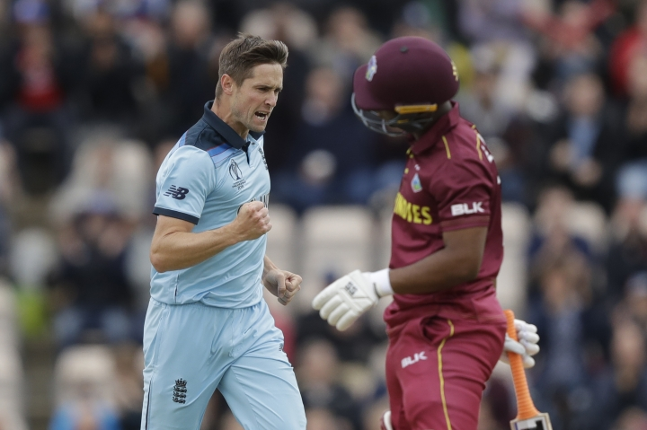 England's Chris Woakes celebrates taking the wicket of West Indies' Evin Lewis, right, during the Cricket World Cup match between England and West Indies at the Hampshire Bowl in Southampton, England, Friday, June 14, 2019. (AP Photo/Matt Dunham)