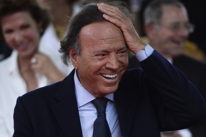 FILE - In this Sept. 29, 2016 file photo, Spain's singer Julio Iglesias smiles during his star unveiling ceremony at the Walk of Fame in San Juan, Puerto Rico. At 75 and after a five-decade-long career, Julio Iglesias keeps performing internationally, driven by his passion and, above all, a relentless discipline. It's something the Spanish crooner says he had to learn early on, after a nearly fatal car accident frustrated his plans to play professional soccer. (AP Photo/Carlos Giusti, File)