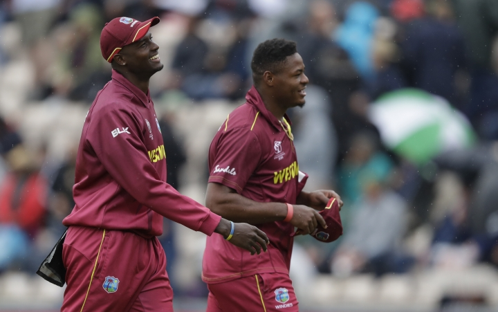 West Indies' captain Jason Holder , left, and West Indies' Oshane Thomas smile as they leave the pitch as rain stops play during the World Cup cricket match between South Africa and the West Indies at The Ageas Bowl in Southampton, Monday, June 10, 2019. (AP Photo/Kirsty Wigglesworth)