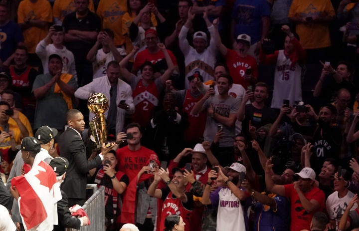 This Thursday, June 13, 2019, photo shows Toronto Raptors general manager Masai Ujiri holding the championship trophy after the Raptors defeated the Golden State Warriors in Game 6 of basketball's NBA Finals in Oakland, Calif. Authorities say they are investigating whether Toronto Raptors president Masai Ujiri pushed and hit a sheriff's deputy in the face as he tried to get on the court after his team won the NBA title in Oakland. (AP Photo/Tony Avelar)
