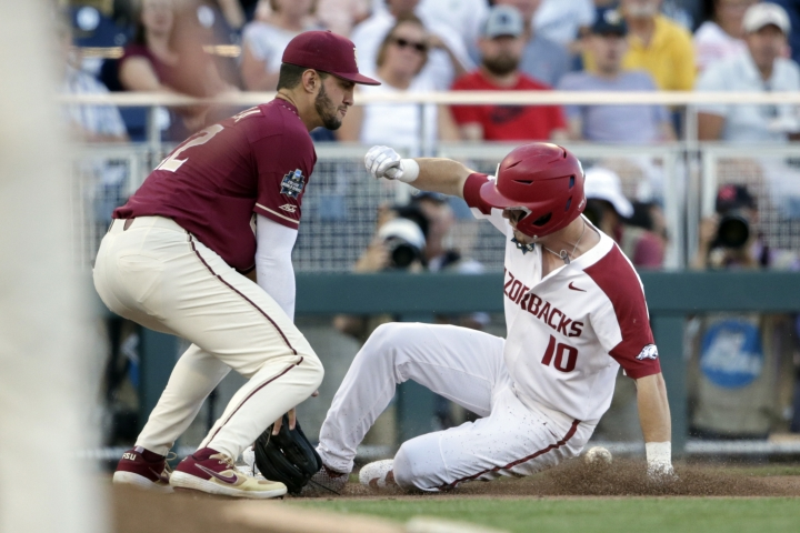 Arkansas' Matt Goodheart (10) is safe at third base ahead of the throw to Florida State third baseman Drew Mendoza on a base hit by Dominic Fletcher in the sixth inning of an NCAA College World Series baseball game in Omaha, Neb., Saturday, June 15, 2019. (AP Photo/Nati Harnik)