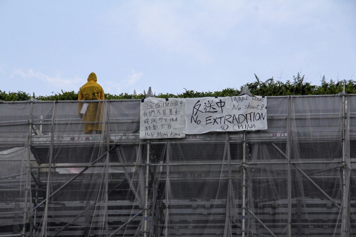 """In this Saturday, June 15, photo, a man wearing a raincoat bearing the words """"Cold blooded black police, Carrie Lam kill Hong Kong"""" stands next to the anti-extradition bill banners hanging on the scaffolding of a shopping mall before he jumped to his death in Hong Kong. Hong Kong was bracing Sunday for another massive protest over an unpopular extradition bill that has highlighted the territory's apprehension about relations with mainland China, a week after the crisis brought as many as 1 million into the streets. (Apple Daily via AP)"""