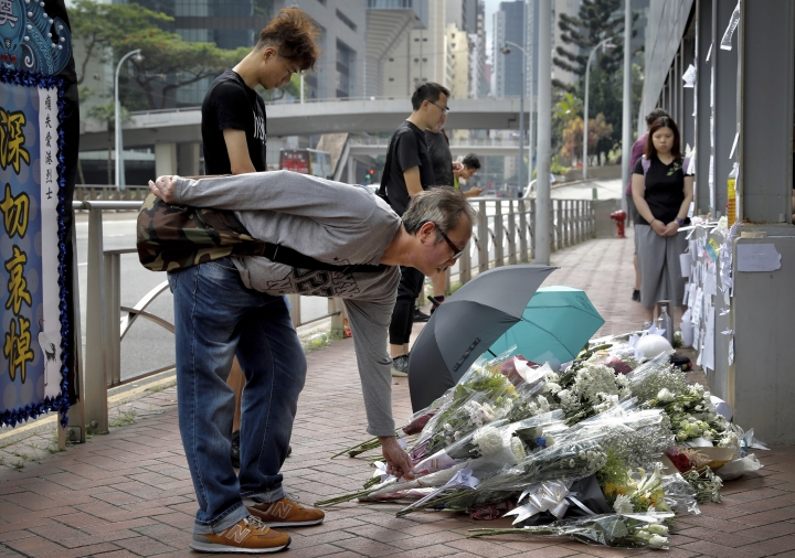 Mourners lay flowers on the site where a man fell to his death a day earlier after hanging a protest banner on the scaffolding of a shopping mall in Hong Kong, Sunday, June 16, 2019. Hong Kong was bracing Sunday for another massive protest over an unpopular extradition bill that has highlighted the territory's apprehension about relations with mainland China, a week after the crisis brought as many as 1 million into the streets. (AP Photo/Vincent Yu)
