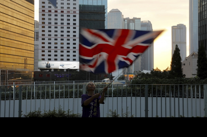 A protester waves a British flag outside the government headquarters in Hong Kong on Saturday, June 15, 2019. Hong Kong's Chief Executive Carrie Lam said she will suspend a proposed extradition bill indefinitely in response to widespread public unhappiness over the measure, which would enable authorities to send some suspects to stand trial in mainland courts. (AP Photo/Vincent Yu)