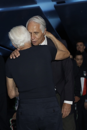 Designer Giorgio Armani, left, greets president of the Italian National Olympic Committee Giovanni Malago at the end of the Emporio Armani men's Spring-Summer 2020 collection, unveiled during the fashion week, in Milan, Italy, Saturday, June 15, 2019. (AP Photo/Luca Bruno)