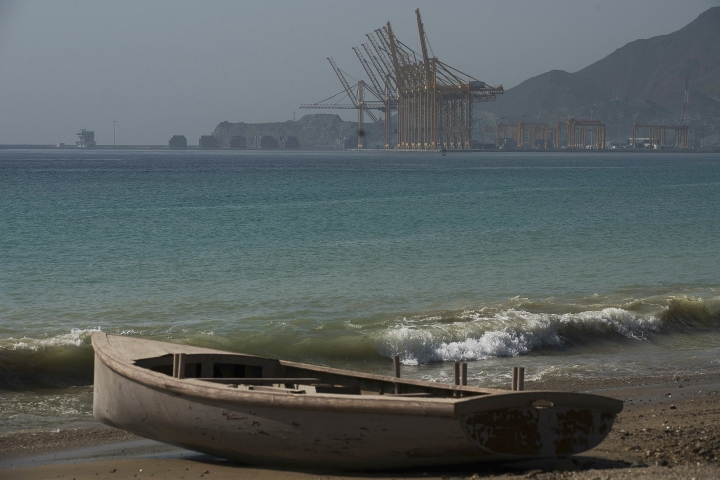 A wooden boat sits on the beach with the Port of Khorfakkan behind it in Khorfakkan, United Arab Emirates, Saturday, June 15, 2019. The Japanese owner of the Kokuka Courageous said Friday, June 14, 2019, that the vessel, one of two oil tankers targeted in an apparent attack in the Gulf of Oman, would be brought to the Emirati port of Khorfakkan. (AP Photo/Jon Gambrell)