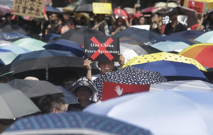 A supporter holds a slogan to oppose the Hong Kong extradition law outside of the Legislative Yuan in Taipei, Taiwan, Sunday, June 16, 2019. Hong Kong residents Sunday continued their massive protest over an unpopular extradition bill that has highlighted the territory's apprehension about relations with mainland China, a week after the crisis brought as many as 1 million into the streets. (AP Photo/Chiang Ying-ying)