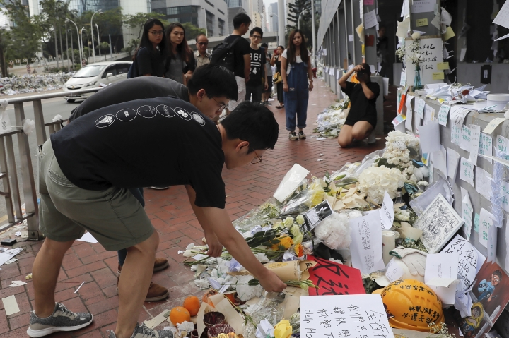 Pro-democracy activist Joshua Wong, second from bottom, and Nathan Law pay respect to a protester who fell to his death after hanging a protest banner against an extradition bill, at a makeshift memorial in Hong Kong, Monday, June 17, 2019. Wong, a leading figure in Hong Kong's 2014 Umbrella Movement demonstrations, was released from prison on Monday and vowed to soon join the latest round of protests. (AP Photo/Kin Cheung)