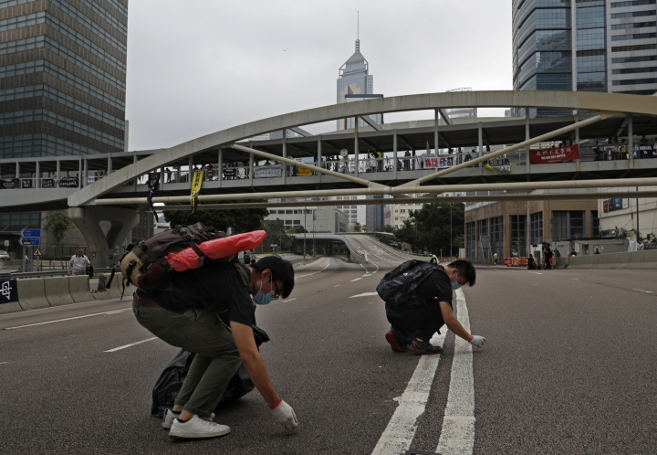 Protesters clean up the main road near the Legislative Council after tens of thousands of protesters staged a massive protest against an extradition bill in Hong Kong, Monday, June 17, 2019. Protesters in Hong Kong have begun leaving the streets and gathering near the city's government headquarters. (AP Photo/Vincent Yu)