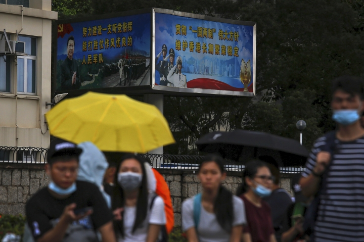 Protesters with umbrellas gather near billboards carrying a photo of Chinese President Xi Jinping and Chinese People's Liberation Army (PLA) near the Legislative Council as they continue to protest against the unpopular extradition bill in Hong Kong, Monday, June 17, 2019. (AP Photo/Kin Cheung)
