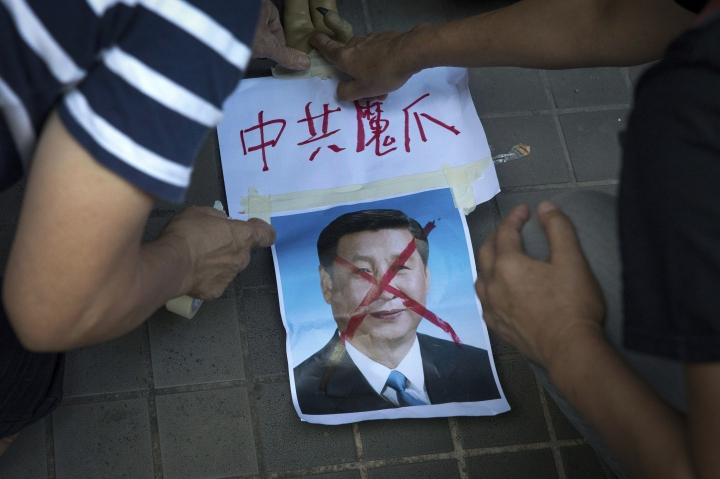 """FILE - In this Saturday, July 1, 2017, file photo, pro-democracy activists paste the words """"Chinese Communist Demon Claws"""" on a defaced photo of Chinese President Xi Jinping before attempting to march in protest towards the venue where official ceremonies are held to mark the 20th anniversary of Chinese rule over Hong Kong in Hong Kong. (AP Photo/Ng Han Guan, File)"""