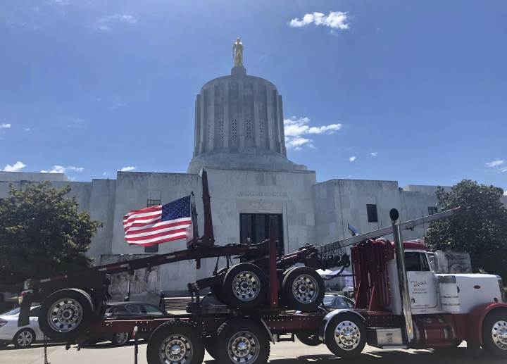 FILE - In this June 12, 2019, file photo, a truck moves around the Oregon state Capitol during a protest against climate bills that truckers say will put them out of business, in Salem, Ore. Oregon is on the precipice of becoming the second state after California to adopt a cap-and-trade program, a market-based approach to lowering the greenhouse gas emissions behind global warming. (AP Photo/Sarah Zimmerman, File)