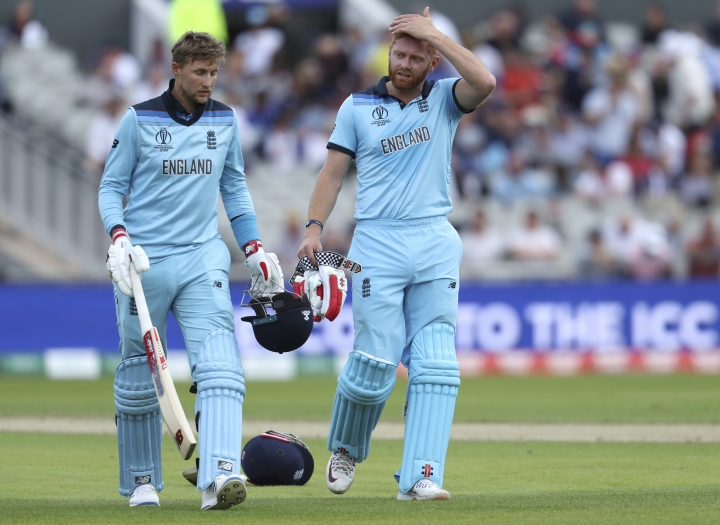 England's Jonny Bairstow, right, and Joe Root walk for a drinks break during the Cricket World Cup match between England and Afghanistan at Old Trafford in Manchester, England, Tuesday, June 18, 2019. (AP Photo/Rui Vieira)