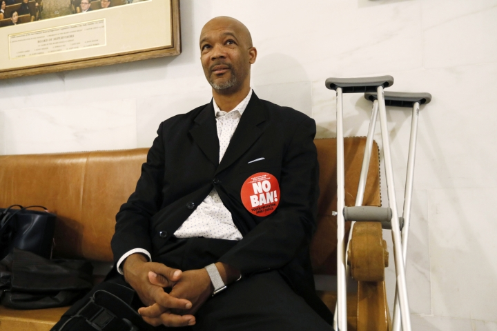 "Floyd Trammell, a pastor at First Friendship Baptist Church, waits outside the chambers prior to the board of supervisors vote on the nation's first ban of e-cigarette sales on Tuesday, June 18, 2019, at City Hall in San Francisco. He wears a ""no ban"" sticker to oppose the measures. San Francisco supervisors unanimously voted to move the city toward becoming the first in the United States to ban all sales of electronic cigarettes in an effort to crack down on youth vaping. The plan would ban the sale and distribution of e-cigarettes, as well as prohibit e-cigarette manufacturing on city property. (AP Photo/Samantha Maldonado)"