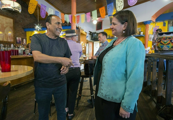 In a Tuesday, May 28, 2019 photo, Mario Rojas of Kansas City speaks with Kansas City mayoral candidate Jolie Justus, right, during a meet and greet with the mayoral candidate at La Fonda in Lawrence, Kans.Two candidates with vastly different life stories but several comparable political views are the Tuesday, June 18, 2019 to become Kansas City's next mayor. (Tammy Ljungblad/The Kansas City Star via AP)