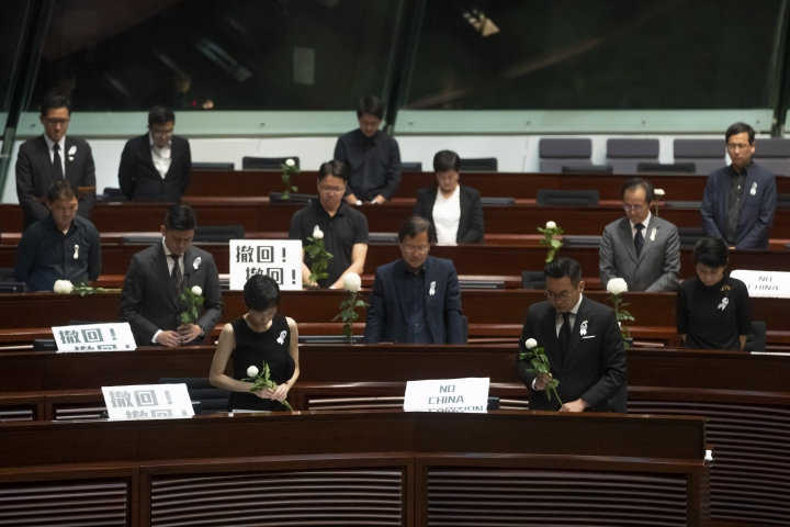"Pro-democracy lawmakers pay a silent tribute to the man who fell to his death on Saturday evening after hanging a protest banner on scaffolding on a shopping mall, at the Legislative Council in Hong Kong, Wednesday, June 19, 2019. Hong Kong lawmakers are meeting for the first time in a week, after massive protests over an extradition bill that eventually was suspended. The placards with Chinese read ""Withdraw"". (AP Photo/Kin Cheung)"