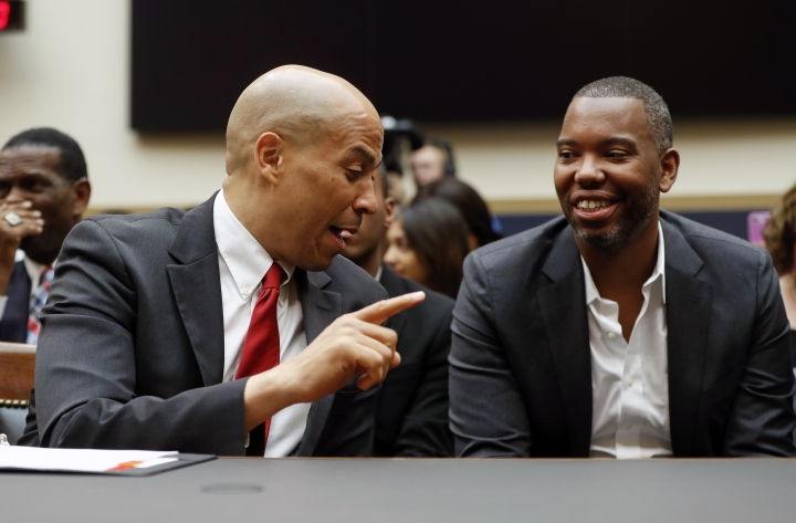 Democratic Presidential candidate Sen. Cory Booker, D-N.J., left, talks with author Ta-Nehisi Coates, right, as he waits to testify about reparation for the descendants of slaves during a hearing before the House Judiciary Subcommittee on the Constitution, Civil Rights and Civil Liberties, at the Capitol in Washington, Wednesday, June 19, 2019. (AP Photo/Pablo Martinez Monsivais)