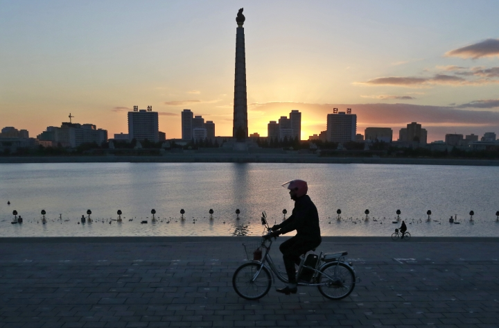 FILE - In this Oct. 27, 2018 file photo, a man rides his electric bike as the Tower of the Juche Idea is silhouetted agains the sunrise in Pyongyang, North Korea. As Chinese President Xi Jinping makes an official trip June 20, 2019 to North Korea, Beijing is anxious to encourage North Korea's self declared shift away from nuclear confrontation toward economic development. (AP Photo/Dita Alangkara, File)