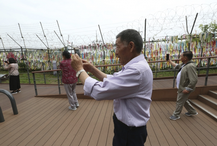 Visitors take photos toward the North's side at the Imjingak Pavilion, near the demilitarized zone of Panmunjom, in Paju, South Korea, Thursday, June 20, 2019. Chinese President Xi Jinping departed Thursday morning for a state visit to North Korea, where he's expected to talk with leader Kim Jong Un about his nuclear program while negotiations have stalled with Washington. (AP Photo/Ahn Young-joon)