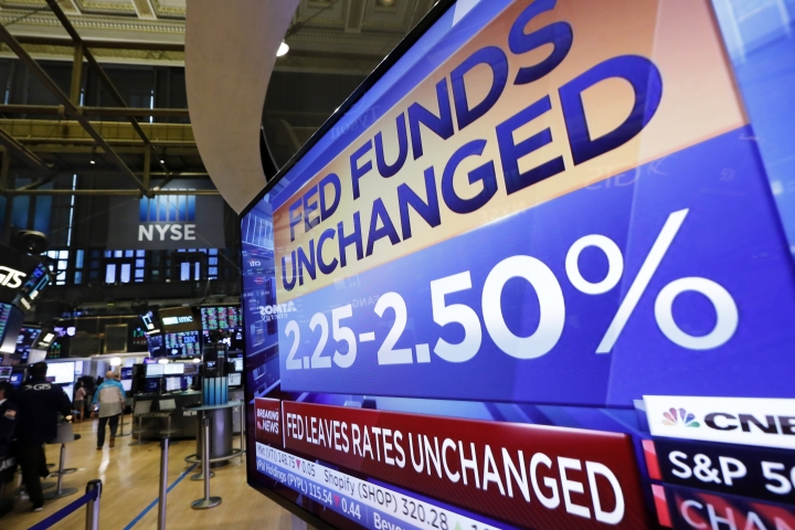 A television screen on the trading floor of the New York Stock Exchange shows the rate decision of the Federal Reserve, Wednesday, June 19, 2019. The Federal Reserve is leaving its key interest rate unchanged but signaling that it's prepared to start cutting rates if needed to protect the U.S. economy from trade conflicts and other threats. (AP Photo/Richard Drew)