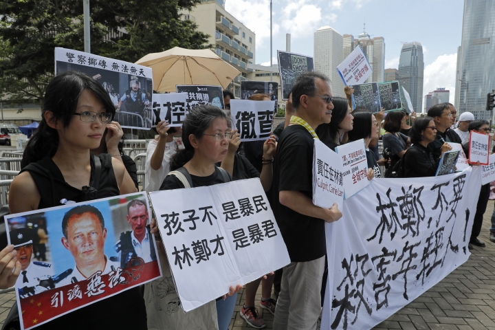 "Activists from various groups including parents and religious hold placards of picture of police commander with Chinese reads ""The child is not rioter, Carrie Lam is the tyrant"", outside the government office demanding to stop shooting their kids in Hong Kong, Thursday, June 20, 2019. A Hong Kong student group demanded Wednesday that the city completely scrap a politically charged extradition bill and agree to investigate police tactics against protesters before a Thursday deadline or face further street demonstrations. (AP Photo/Kin Cheung)"