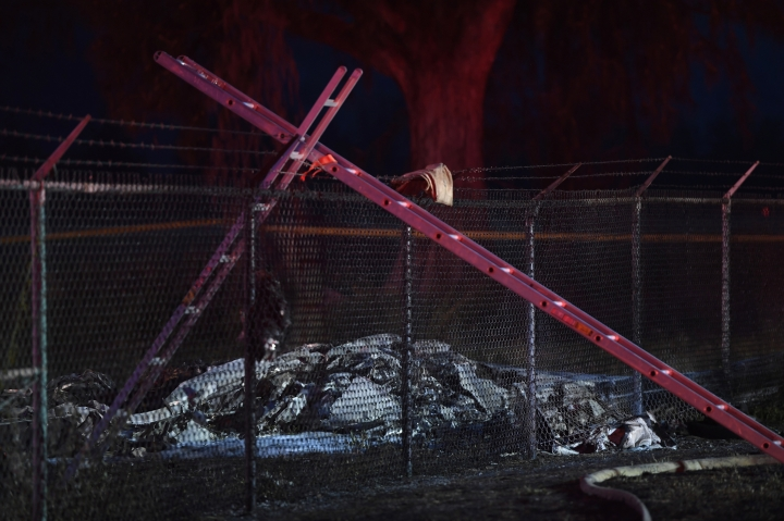 Remnants of an aircraft carrying nine people lies on the ground near a fence that surrounds Dillingham Airfield in Mokuleia, just off Farrington Highway, Friday, June 21, 2019. Nine people on board the twin engine aircraft died Friday night in a crash on Oahu's North Shore, officials said. (Bruce Asato/Honolulu Star-Advertiser via AP)