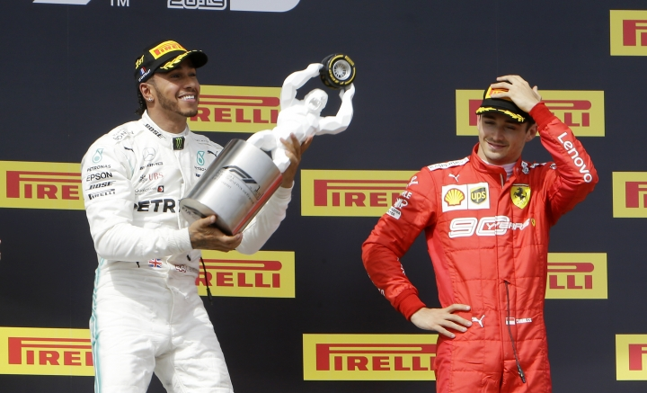 Mercedes driver Lewis Hamilton, left, of Britain, celebrates on the podium after winning the French Formula One Grand Prix at the Paul Ricard racetrack as third placed Ferrari driver Charles Leclerc of Monaco looks him, in Le Castellet, southern France, Sunday, June 23, 2019. (AP Photo/Claude Paris)