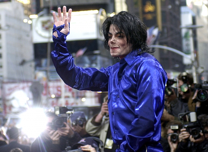 "FILE - In this Nov. 7, 2001 file photo, Michael Jackson waves to crowds gathered to see him at his first ever in-store appearance to celebrate his new album ""Invincible"" in New York. As the 10th anniversary of Jackson's death approaches, experts say his music legacy is still going strong despite the documentary's detailed abuse allegations. (AP Photo/Suzanne Plunkett, File)"