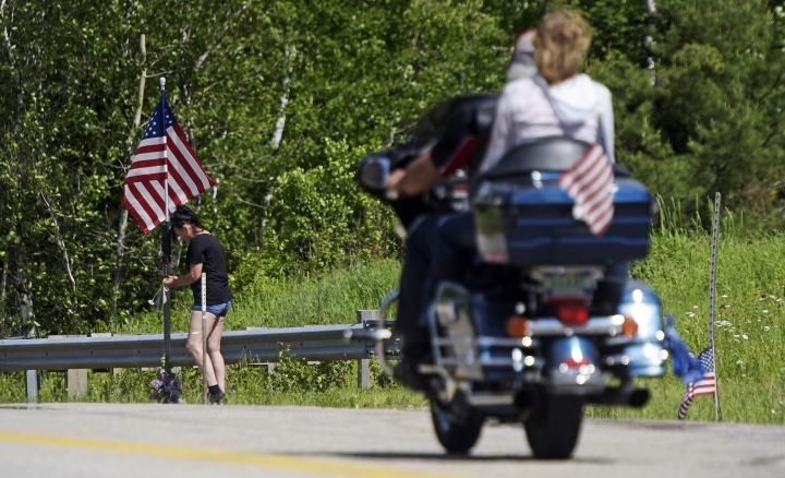 A motorcycle passes as a woman leaves flowers at the scene of a fatal accident on Route 2 in Randolph, N.H., Saturday, June 22, 2019. Investigators pleaded Saturday for members of the public to come forward with information that could help them determine why a pickup truck hauling a trailer collided with a group of motorcycles on a rural highway. (Paul Hayes/Caledonian-Record via AP)