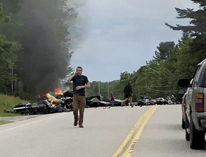 This photo provided by Miranda Thompson shows a man talking on his cellphone at the scene where several motorcycles and a pickup truck collided on a rural, two-lane highway Friday, June 21, 2019 in Randolph, N.H. New Hampshire State Police said a 2016 Dodge 2500 pickup truck collided with the riders on U.S. 2 Friday evening. The cause of the deadly collision is not yet known. The pickup truck was on fire when emergency crews arrived. (Miranda Thompson via AP)