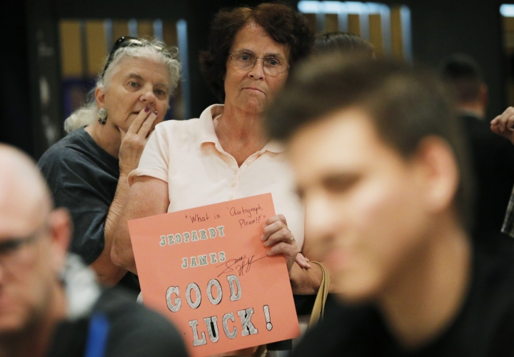 """""""Jeopardy!"""" fans Judi Blomquist, holding sign, and Susan Youngblood watch as """"Jeopardy!"""" champion and professional sports gambler James Holzhauer, right, plays in a tournament at the World Series of Poker, Monday, June 24, 2019, in Las Vegas. (AP Photo/John Locher)"""