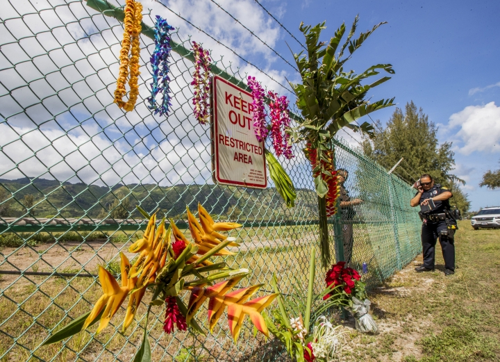 A memorial is seen at the site where a Beechcraft King Air twin-engine plane crashed Friday evening killing multiple people near the chain link fence surrounding Dillingham Airfield in Mokuleia, Hawaii. Police and sheriffs patrol the area. No one aboard survived the skydiving plane crash. The flight was operated by the Oahu Parachute Center skydiving company. (Dennis Oda/Honolulu Star-Advertiser via AP)