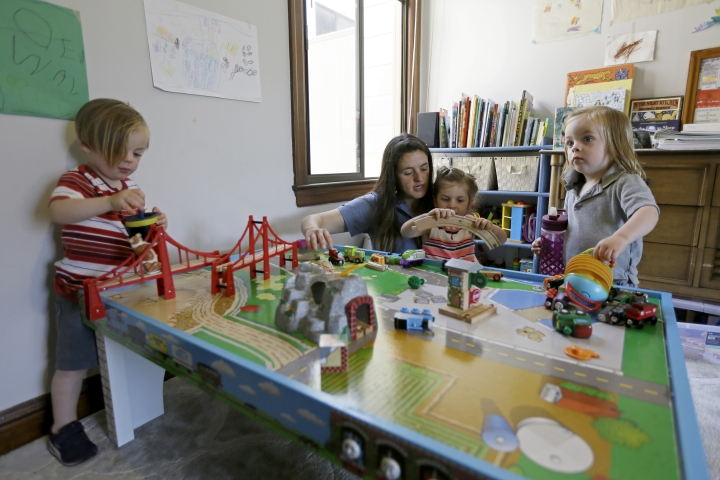 In this Thursday, June 6, 2019 photo, Sarah Montoya plays with her daughter, Walden, and twins Farallon, right, and Nicasio, left, at their home in San Francisco. During last year's deadly Camp Fire, which killed 85 people and destroyed 14,000 homes, smoke from the blaze inundated a San Francisco neighborhood roughly 170 miles away where Montoya lives with her husband, Trevor McNeil, and their three children. All three children have respiratory problems suspected to be asthma. But when the smoke from the Camp Fire filled the air for two weeks, the family was unable to find child-sized face masks to protect them or an air filter to clear the air in their house. (AP Photo/Eric Risberg)