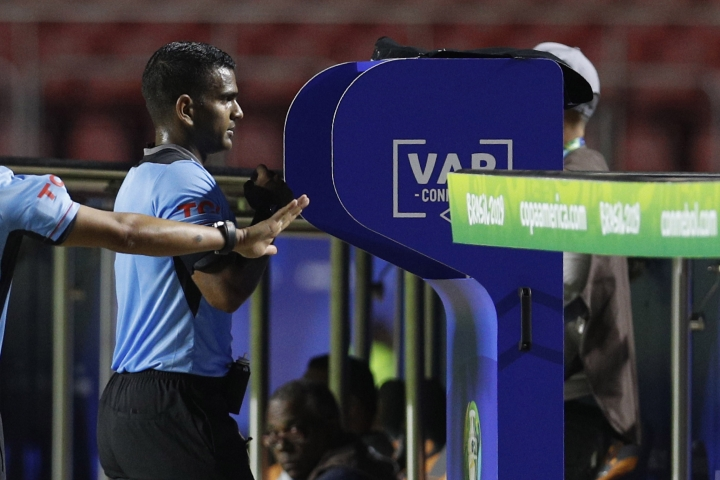Referee Alexis Herrera reviews a play on the VAR stand during a Copa America Group B soccer match between Colombia and Qatar at Morumbi stadium in Sao Paulo, Brazil, Wednesday, June 19, 2019. (AP Photo/Victor R. Caivano)