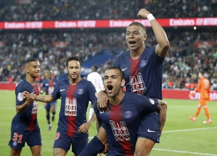 FILE - In this April 21, 2019 file photo, PSG's Kylian Mbappe, top, celebrates with teammate Dani Alves after scoring the third goal during the French League One soccer match between Paris-Saint-Germain and Monaco at the Parc des Princes stadium in Paris. After lifting the World Cup with France last summer, Mbappe now wants to win the European championships and a gold medal at the Tokyo Olympics next year. (AP Photo/Michel Euler, File)
