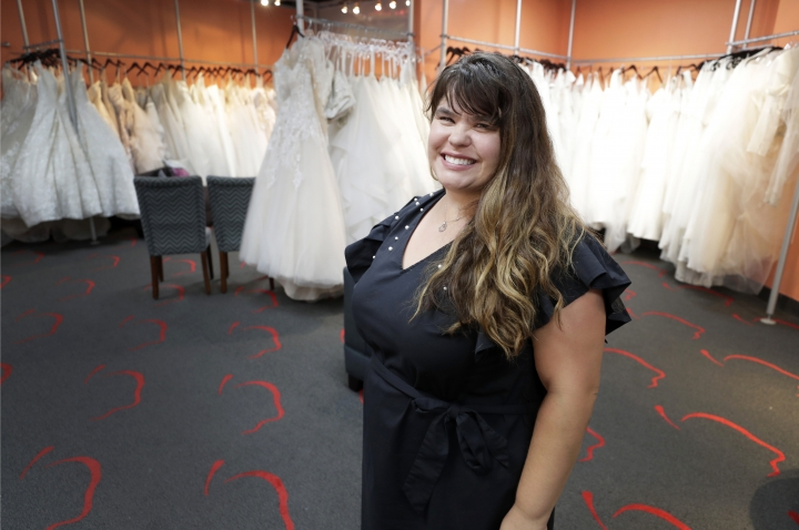 In this Friday, June 21, 2019, photo Ann Campeau, owner of Strut Bridal, stands in her shop in Tempe, Ariz. Cut-rate prices on websites that sell wedding dresses direct from China put pressure on Campeau, who owns four bridal shops in California and Arizona. She has had customers come in after seeing low-end gowns online and expecting to get a dress at a similar price. (AP Photo/Matt York)