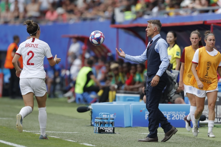 England head coach Philip Neville passes the ball to England's Lucy Bronze, left, during the Women's World Cup round of 16 soccer match between England and Cameroon at the Stade du Hainaut stadium in Valenciennes, France, Sunday, June 23, 2019. (AP Photo/Michel Spingler)