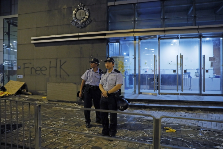 Riot police stand guard at a entrance after they clear barricades blocked by protesters outside the police headquarters as thousands gathered to demand for an independent inquiry into a heavy-handed police crackdown at a protest earlier this month, in Hong Kong during the early hours of Thursday, June 27, 2019. Thousands of people joined Hong Kong's latest protest rally Wednesday night against legislation they fear would erode the city's freedoms, capping a daylong appeal to world leaders ahead of a G-20 summit this week that brings together the heads of China, the United States and other major nations. (AP Photo/Kin Cheung)