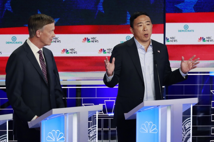 Democratic presidential candidate entrepreneur Andrew Yang, right, speaks during the Democratic primary debate hosted by NBC News at the Adrienne Arsht Center for the Performing Arts, Thursday, June 27, 2019, in Miami, as former Colorado Gov. John Hickenlooper listens. (AP Photo/Wilfredo Lee)