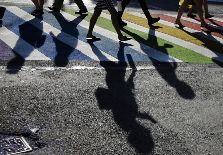 Pedestrians cross the intersection of Christopher Street and Seventh Avenue near the Stonewall Inn Thursday, June 27, 2019, in New York. (AP Photo/Frank Franklin II)