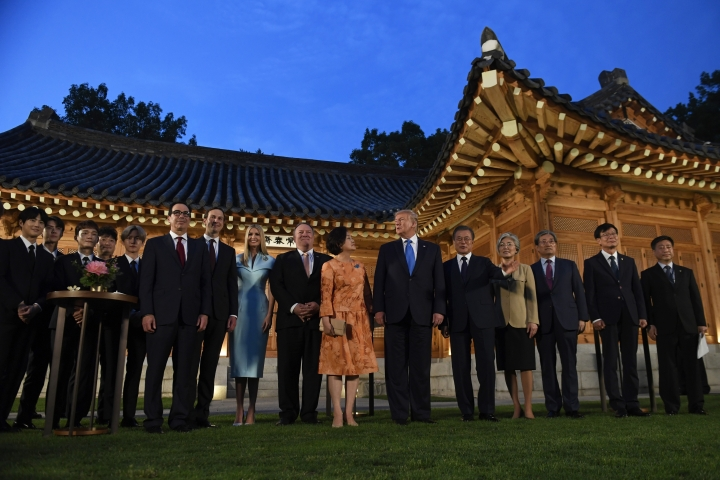 President Donald Trump, center, and South Korean President Moon Jae-in, fifth right, pose for a group photo with guests during a visit to the tea house on the grounds of the Blue House in Seoul, South Korea, Saturday, June 29, 2019. Trump is making a quick trip to Seoul after attending the G-20 summit in Osaka, Japan. (AP Photo/Susan Walsh)