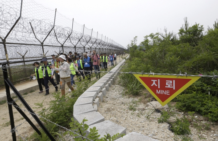 FILE - In this June 14, 2019, file photo, hikers and journalists walk along the DMZ Peace Trail in the demilitarized zone in Goseong, South Korea. Eyeing a history-making photo opportunity, U.S. President Donald Trump on Saturday, June 29, 2019, issued a Twitter invitation to North Korea's Kim Jong Un to join him for a hand shake during a visit by Trump to the demilitarized zone with South Korea. (AP Photo/Ahn Young-joon, File)