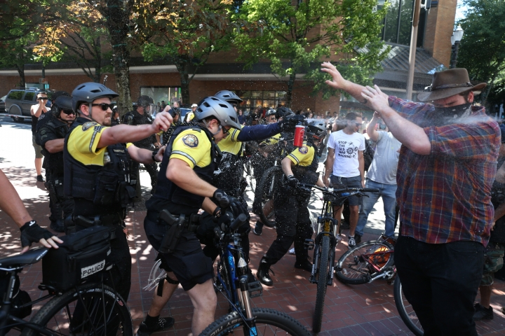 After a confrontation between authorities and protestors, police use pepper spray as multiple groups, including Rose City Antifa, the Proud Boys and others protest in downtown Portland, Ore., on Saturday, June 29, 2019. In separate social media posts later in the day, police declared the situation to be a civil disturbance and warned participants faced arrest. (Dave Killen/The Oregonian via AP)