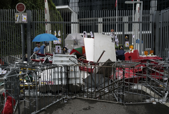 A worker cleans up the main entrance outside government headquarters in Hong Kong, Tuesday, July 2, 2019. Protesters in Hong Kong took over the legislature's main building Monday night, tearing down portraits of legislative leaders and spray painting pro-democracy slogans on the walls of the main chamber. (AP Photo/Vincent Yu)