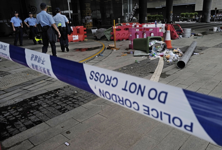 Police officers stand guard outside Legislative Council building in Hong Kong, Tuesday, July 2, 2019. Hundreds of protesters swarmed into Hong Kong's legislature Monday night, defacing portraits of lawmakers and spray-painting pro-democracy slogans in the chamber before vacating it as riot police cleared surrounding streets with tear gas and then moved inside. (AP Photo/Vincent Yu)