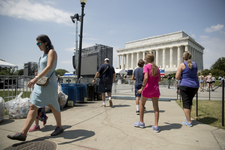 "Visitors to the National Mall walk near the Lincoln Memorial as workers set up for President Donald Trump's 'Salute to America' event honoring service branches on Independence Day, Tuesday, July 2, 2019, in Washington. President Donald Trump is promising military tanks along with ""Incredible Flyovers & biggest ever Fireworks!"" for the Fourth of July. (AP Photo/Andrew Harnik)"